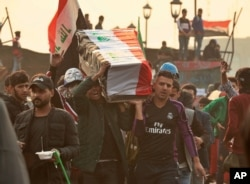 Anti-government protesters carry a symbolic coffin during protests in Baghdad, Iraq, Nov. 29, 2019.