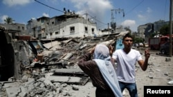 Palestinians react to the destruction of homes in the Shijaiyah neighborhood, which was heavily shelled by Israel during fighting, in Gaza City July 20, 2014.