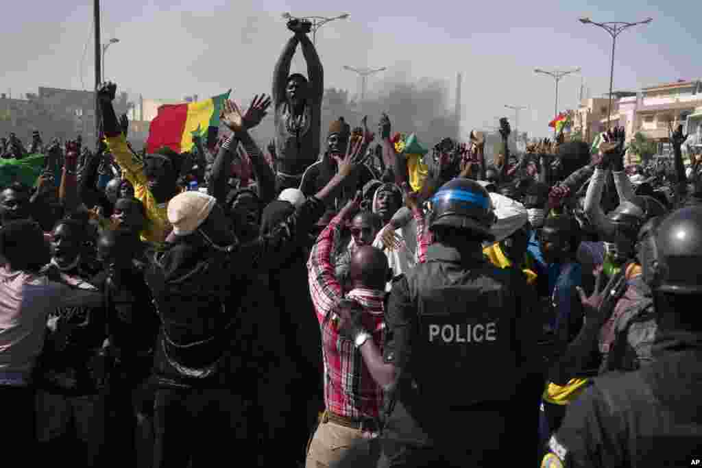 Demonstrators shout slogans in front of riot policemen during a protest against the arrest of opposition leader and former presidential candidate Ousmane Sonko, Senegal.