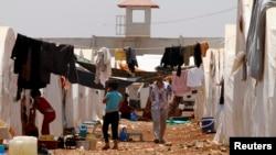 FILE - Syrian refugees walk under clothing lines at the Bab Al-Salam refugee camp in Azaz, near the Syrian-Turkish border, June 9, 2013.