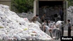 지난 2009년 북한 접경도시 신의주에서 북한 주민들이 중국으로부터 수입한 밀가루 포대를 트럭에 싣고 있다. 압록강 건너 중국 단둥에서 바라본 모습이다. (자료사진)