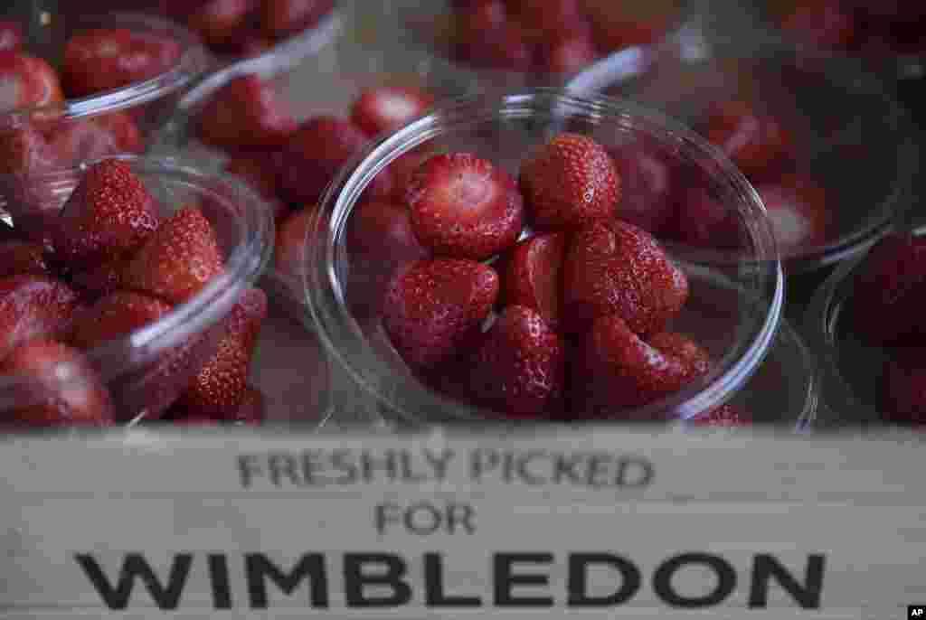 Buah-buahan stroberi terlihat ditata rapi untuk menarik pembeli, pada hari kelima Kejuaraan Tenis Wilmbledon di London. Rumput hijau, (kostum) putih (yang dikenakan oleh para atlet) tenis dan warna merah buah stroberi. Hanya pada saat Wimbledon - meskipun tidak ada yang benar-benar tahu bagaimana buah musiman tersebut menjadi berada di mana-mana di All England Club.