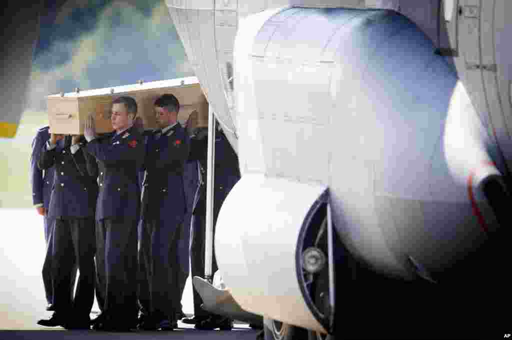 Pallbearers carry a coffin out of a military transport plane during a ceremony for the return of the first bodies of passengers and crew members killed in the downing of Malaysia Airlines Flight MH17, Eindhoven Air Base, Eindhoven, Netherlands, July 23, 2014.