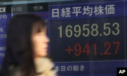 FILE - A woman walks past an electronic stock board showing Japan's Nikkei 225.