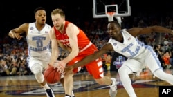 Syracuse's Trevor Cooney (10) drives against North Carolina's Nate Britt (0) and Theo Pinson (1) during the first half of the NCAA Final Four tournament college basketball semifinal game Saturday, April 2, 2016, in Houston. (AP Photo/David J. Phillip)
