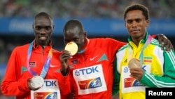 Abel Kirui du Kenya, au centre sur le podium, présente se médaille aux côtés de son compatriote Vincent Kipruto, médaillé d'argent, à gauche, et de l'Ethiopien Feyisa Lilesa, médaillé de bronze, à droite, après l'épreuve du marathon version masculine, aux Championnats du monde de l'IAAF à Daegu, 4 septembre 2011
