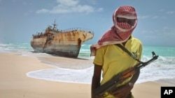 FILE - In this 2012 photo, a Somali pirate stands near a Taiwanese fishing vessel washed ashore after the pirates were paid a ransom and the crew were released.