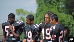 Samee Khan, 14, (second from left) abstains during a water break at football practice because he is observing the Ramadan fast.