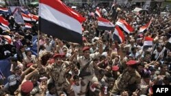 Binh sĩ Yemen cùng người biểu tình hô khẩu hiệu và vẫy cờ ăn mừng việc Tổng thống Ali Abdullah Saleh rời khỏi nước sang Ả Rập Xê-út để điều trị y khoa, ngày 5/6/2011