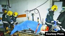澳门救援者在恒德大厦地库停车场再发现一名死者。(苹果日报图片)