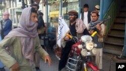 29일 아프가니스탄 쿤두즈에서 탈레반 병사가 탈레반 깃발이 꽂힌 오토바이를 타고 있다.