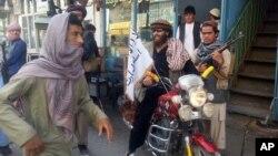 Un combattant taliban est assis sur sa moto ornée d'un drapeau taliban dans une rue à Kunduz, en Afghanistan (AP - 29 sept 2015)