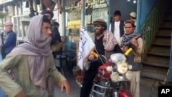 یک پیکارجوی طالبان با پرچم این گروه روی یک موتور در قندوز نشسته است - ۲۹ سپتامبر ۲۰۱۵