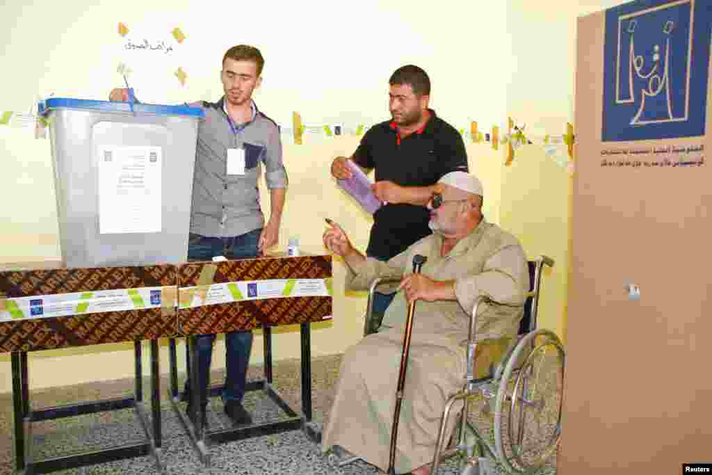An elderly Iraqi man in a wheelchair receives help as he votes during Iraq's provincial elections at a polling station in Mosul, 390 km north of Baghdad, June 20, 2013.