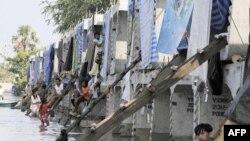 Một số gia đình trong khu vực bị lụt ở ngoại ô Bangkok tạm trú tại một công trường nơi nhiều bloc bằng xi măng được tồn trữ để xây một chiếc cầu cho tuyến xe lửa