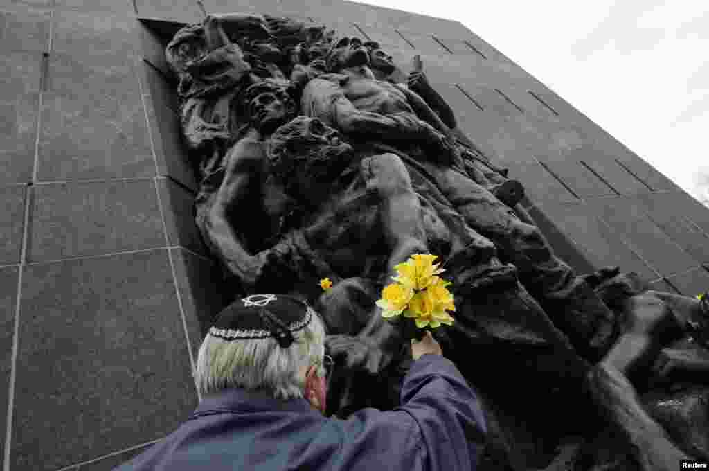 A man places a bunch of flowers at the Monument to the Ghetto after a ceremony commemorating the 70th anniversary of the Warsaw Ghetto Uprising in Warsaw, Poland.