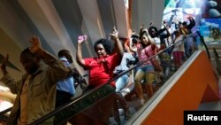 Civilians escape an area at the Westgate Shopping Centre in Nairobi September 21, 2013. Gunmen stormed the shopping mall in Nairobi on Saturday killing at least 20 people in what Kenya's government said could be a terrorist attack, and sending scores flee