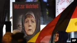 """ARSIP – Sebuah poster dengan bunyi """"Keberanian untuk Berbicara Jujur"""" menggambarkan Kanselir Jerman, Angela Merkel, mengenakan hijab di depan gedung Reichstag dengan bulan sabit di atasnya dalam sebuah demonstrain gerakan anti Islamisasi, Legida, gerakan turunan Pegida, di Leipzing, Jeman, 30 Januari 2015 (foto: AP Photo/Jens Meyer)"""