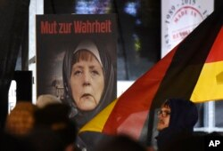 "FILE - A poster with the writing ""Courage to speak the truth"" depicts German Chancellor Angela Merkel wearing a veil during a demonstration of the Legida anti-Islamization movement, an offshoot of Pegida, in Leipzig, Jan. 30, 2015."