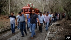 Members of the Solecito search group carry the coffin of Pedro Huesca, a police detective who disappeared in 2013 and whose body was recently found in a mass grave, as they walk to the cemetery in Palmas de Abajo, Veracruz, Mexico, March 8, 2017. Huesca's remains are part of a collection of more than 250 skulls found over the last several months in what appears to be a drug cartel mass burial ground on the outskirts of the city of Veracruz, prosecutors said Tuesday.