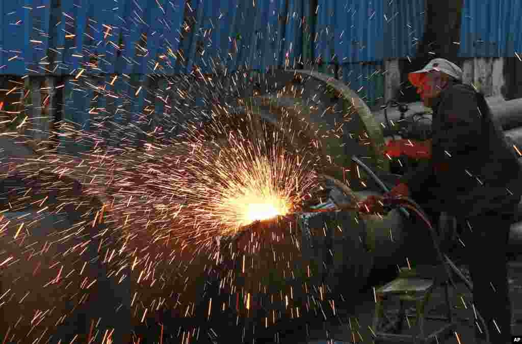An Indian worker works at an iron and steel scrap workshop at an industrial area in Mumbai.