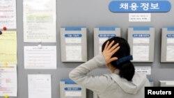 한국 서울에서 한 여성이 구인 게시판을 보고 있다.