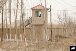 FILE - A security person watches from a guard tower around a detention facility in Yarkent County in northwestern China's Xinjiang Uyghur Autonomous Region, March 21, 2021.