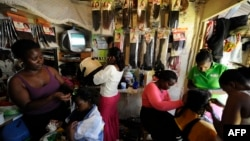 FILE - Kenyan hairdressers attend to clients at a salon in the capital Nairobi, Kenya.
