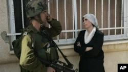 A Palestinian woman stands next to an Israeli soldier during a protest against the expansion of a Jewish settlement near the West Bank village of Nabi Saleh, Friday, Oct. 22, 2010.