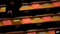 FILE - A delegate walks past copies of draft resolutions placed on delegates' desks of the annual National People's Congress in Beijing's Great Hall of the People, March 16, 2016. A revised controversial law that seeks to harshly regulate foreign NGOs in China is under review by the country's lawmakers.