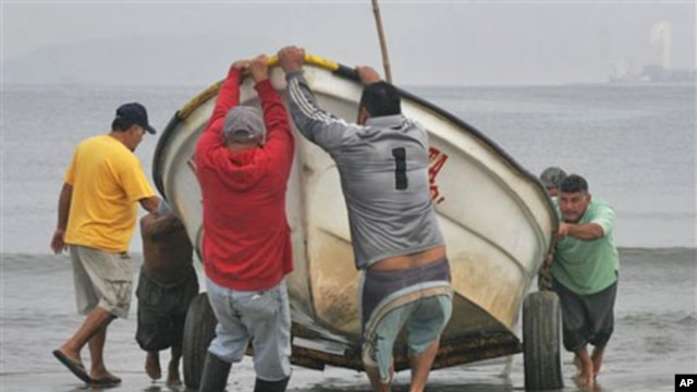 Fishermen pull a boat from the sea in preparation for a possible tsunami in the Pacific resort city of Mazatlan, Mexico, March 11, 2011