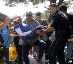Припадник на македонската полиција помага на бремена жена на границата близу Гевгелија