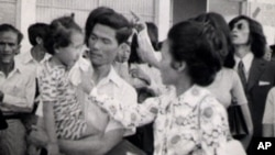 Neou Sarem says goodbye to her husband, Nuon Sari, and her 3-year old daugther, Nuon Sari Sakhura, at Pochentong Airport, 1974.
