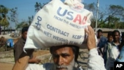 A Bangladeshi man receives food aid from USAID following Cyclone Sidr in 2007.