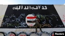 عراق میں حشد الشعبی سے تعلق رکھنے والا ایک جنگجو دیوار پر داعش کے جھنڈے کے سامنے کھڑا ہے۔ (فائل فوٹو)