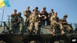 Thủ tướng Ukraine Arseniy Yatsenyuk ngồi giữa các binh sĩ Hoa Kỳ và Ukraine trên một chiếc xe chống đạn ở khu vực Lviv, miền tây Ukraine, 3/6/2015.