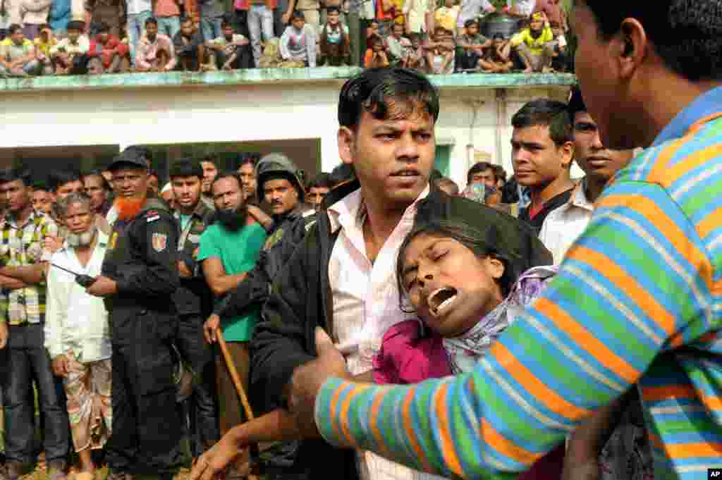 People console a woman whose relative was killed in a fire at a garment factory outside Dhaka, Bangladesh, November 25, 2012.