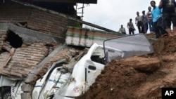 Regu penyelamat memeriksa kerusakan akibat tanahh longsor di kawasan desa Banaran, Ponorogo, Jawa Timur, 1 April 2017. (Foto:AP/Firdaus)