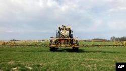 Petani Rick Clifton mengendarai traktor di salah satu ladangnya, menyemprotkan herbisida untuk melindungi tanamannya selama musim gugur dan musim dingin di Orient, Ohio, 5 April 2021. (AP Photo/John Flesher)