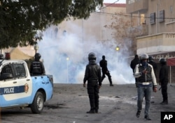 Police forces stand by tear gas during clashes in the city of Ennour, near Kasserine, Tunisia, Wednesday, Jan. 20, 2016.