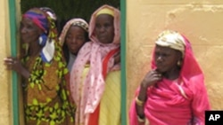 Women peer out of a doorway at the Kwali rehabilitation center for fistula in Kano, northern Nigeria, August 17, 2005.