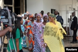 FILE - Some of the 21 Chibok schoolgirls released by Boko Haram follow Minster of Women Affairs Aisha Alhassan after their visit to meet President Muhammadu Buhari In Abuja, Nigeria Oct. 19, 2016