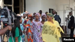 FILE - Some Chibok schoolgirls released by Boko Haram follow Minster of Women Affairs Aisha Alhassan after their visit to meet President Muhammadu Buhari In Abuja, Nigeria Oct. 19, 2016