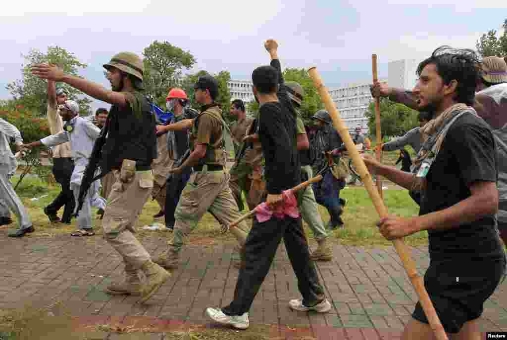 Demonstrators chant while walking with soldiers from the Pakistan Rangers, Islamabad, Sept. 1, 2014.