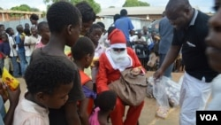 Santa Claus shares sweets and other gifts with students at the Jacaranda School for Orphans (VOA/L. Masina)