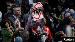 Seorang delegasi mengangkat poster anti-Trans-Pacific Partnership (TPP) di Konvensi Nasional Partai Demokrat Senin (25/7).