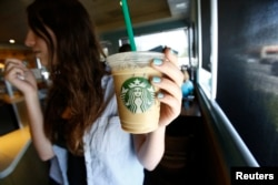 FILE - A patron holds an iced beverage at a Starbucks coffee store in Pasadena, Calif., July 25, 2013. Straws and stirrers are among the top 10 items found in coastal trash cleanups.