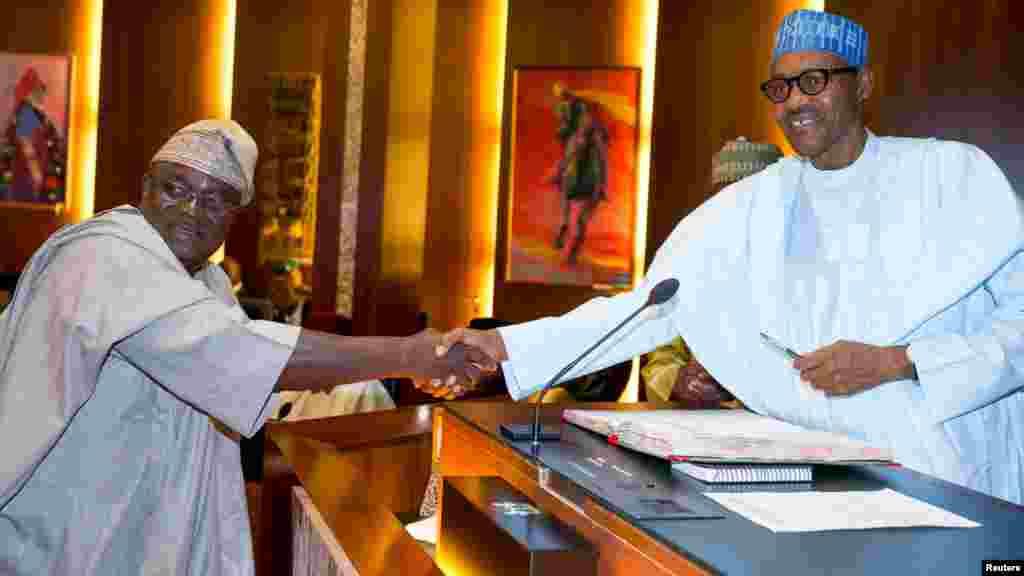 Shugaba Muhammadu Buhari yana gaida kwamishinan INEC na kasa, Adedeji Shoyebi, jim kadan bayan rantsar da shi a Abuja, a ran litinin 9 Nuwamba 2015.