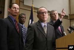 Dallas Mayor Mike Rawlings, right, takes a question as Dr. Daniel Varga, chief clinical officer at Texas Health Presbyterian Hospital, second from right, and other attend a news conference in Dallas, Oct. 15, 2014.