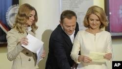 10月9号波兰总理图斯克(中)和妻子(右)、女儿(左)在议会选举中投票